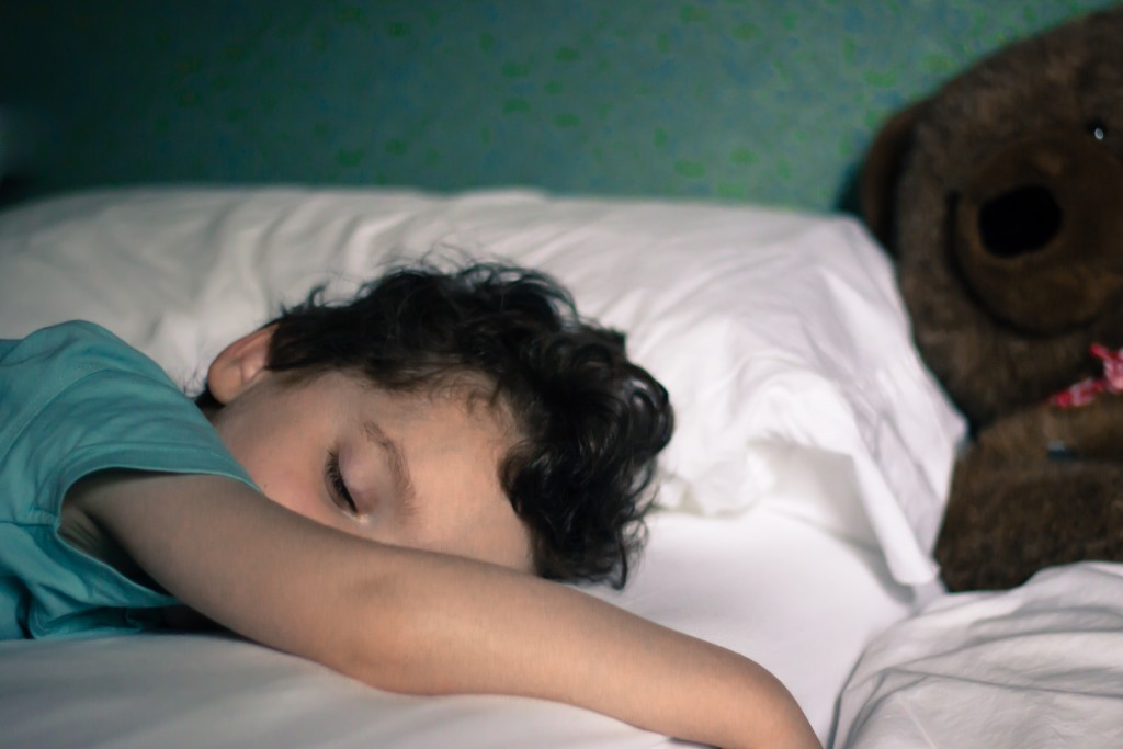Young child sleeping in bed with teddy in background. Sleep apnea in children like him affect their learning.