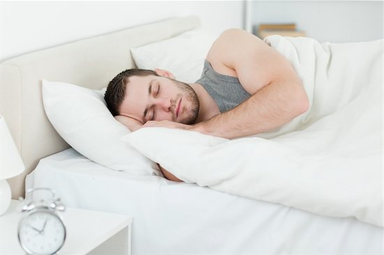A man is sleeping bed next to his alarm clock. Bad sleeping habits like oversleeping can increase the risk for diabetes in men.