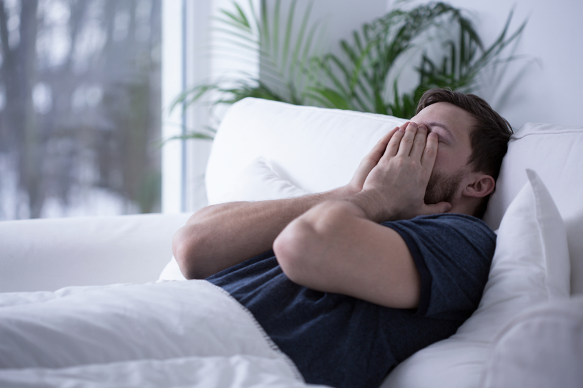 A man is laying in bed, covering his face with his hands as he yawn. Sleep-disturbance warning on drugs seek to prevent scenarios like this one.