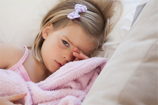 A little girl, who appears restless in bed due to sleep loss.