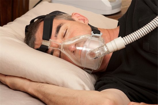 A man is sleeping in bed. He is wearing one of many CPAP machines given to patients with sleep apnea.