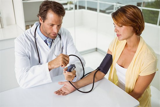 A male doctor is checking blood pressure of a young woman at a medical office, in order to find out if she has hypertension.