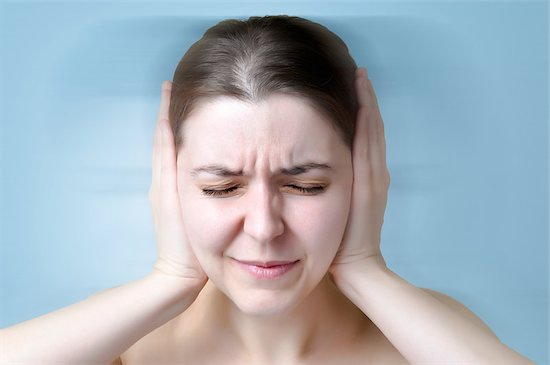 Young woman is covering her ears due to her tinnitus symptoms.