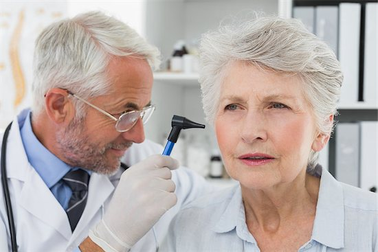 A male doctor is checking an elderly woman's ear to see if she needs a cochlear implant.