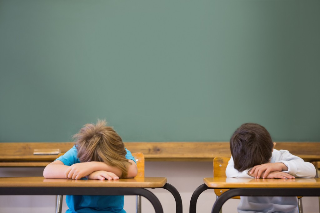 An image of two preschoolers with their heads on top of a school desk, which is a result of sleep deprivation in kids.