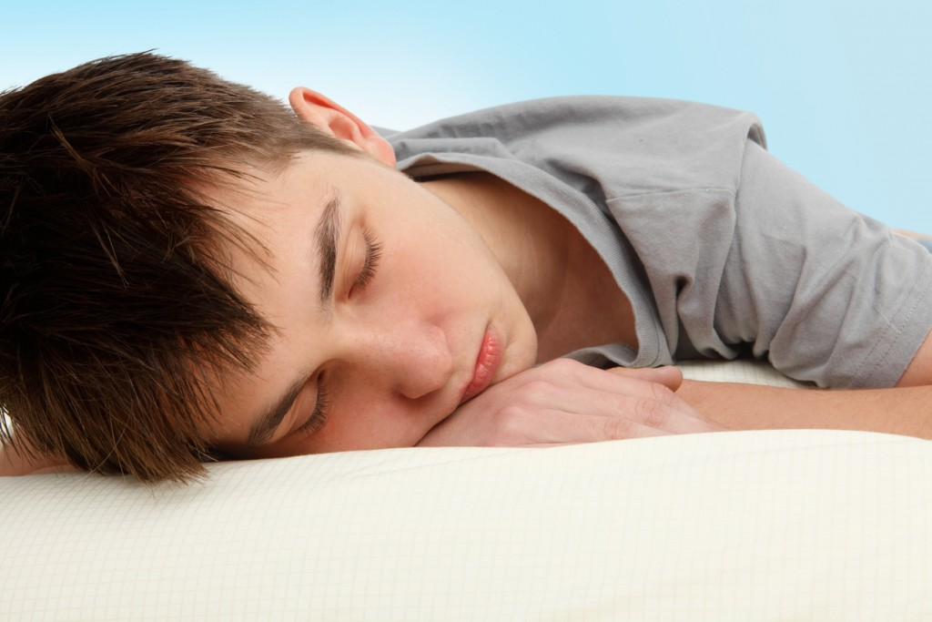An image of good sleeping habits. It depicts a close up shot of a young boy, asleep in bed.