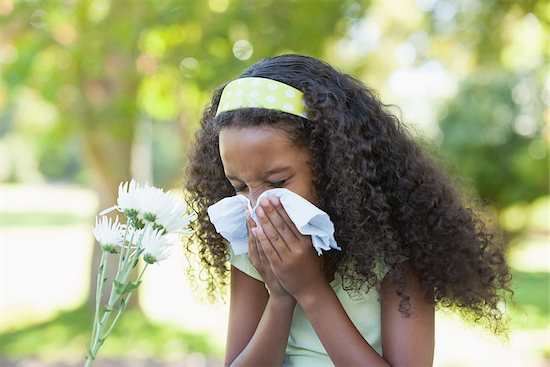 An image of a young girl sneezing due to a flower and childhood allergies.