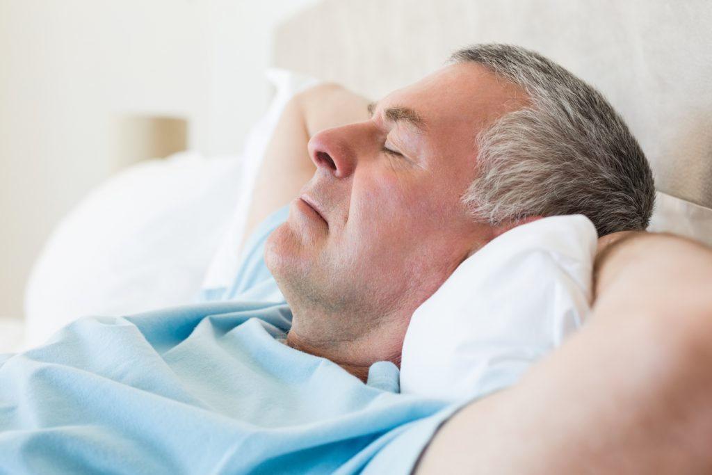 A close-up of an older man napping in his bed, which in one of many irregular sleeping habits.