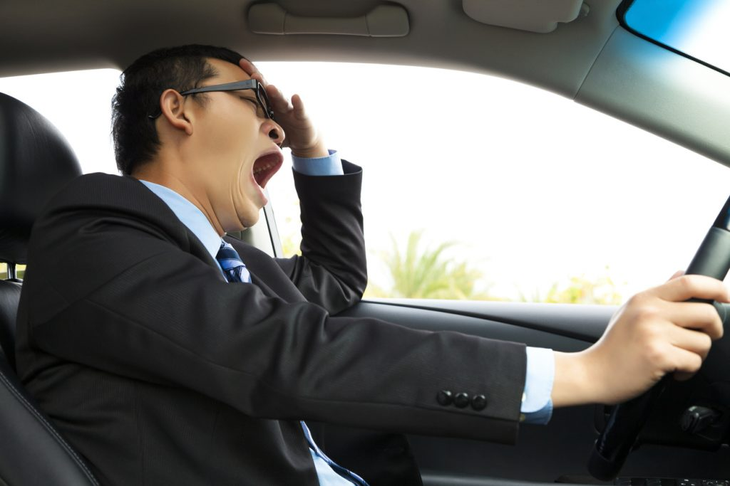 An exhausted driver, who is missing sleep, yawning and driving a car.