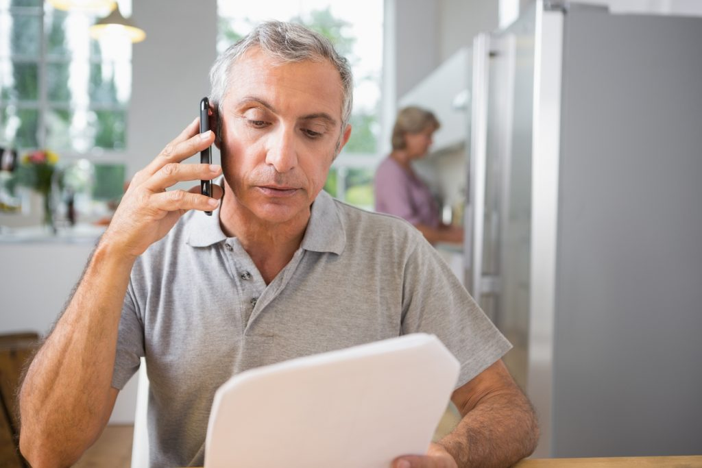 An image of an older gentleman holding a phone up to his ear. He might have trouble processing speech.