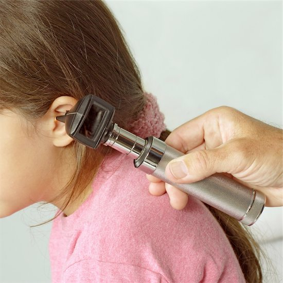 A close-cropped image of a doctor examining the ear of a young girl with a otoscope, checking for an ear infection.