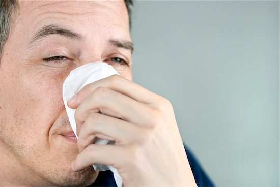 A close-up of a man holding a tissue on his nose and dealing with a sinus infection.