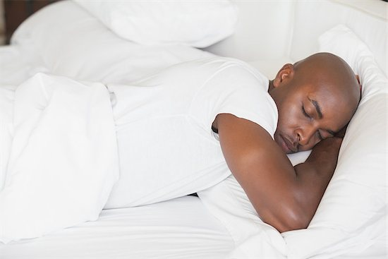 A peaceful man sleeping in bed at home in the bedroom, receiving sleep benefits.