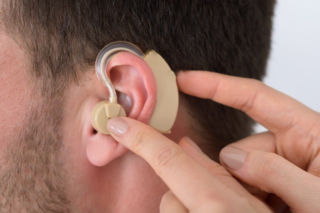 A patient fitting a device on his ear after a cochlear implantation.