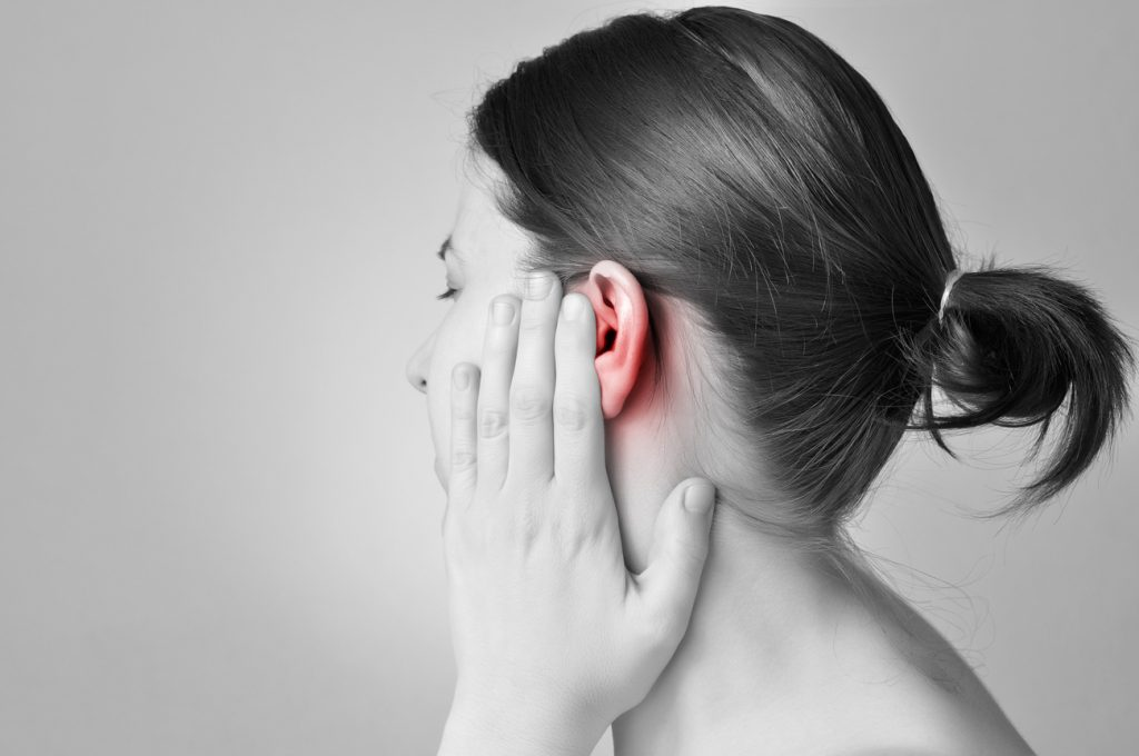A young woman touching her ear (which is red) because she it dealing with severe tinnitus.