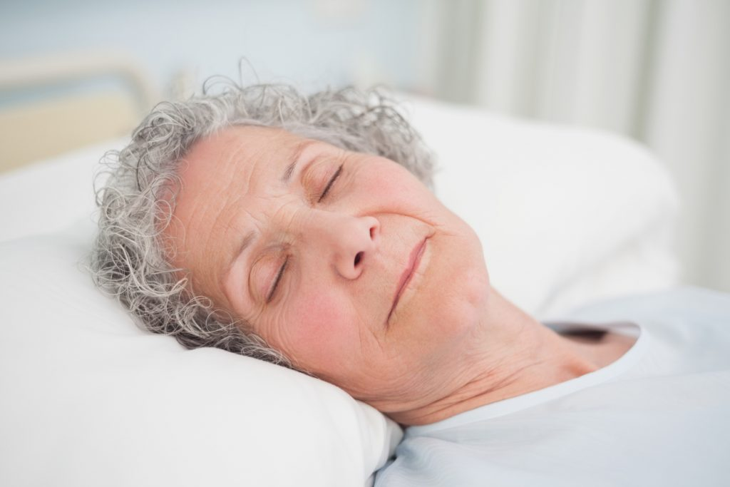 Patient in deep sleep on a medical bed in hospital ward.