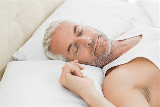 A man in bed, laying down, with a sleep apnea condition.