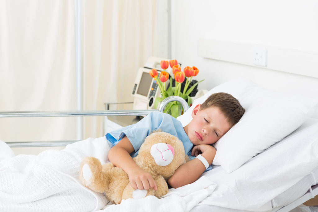 Sick boy in a hospital bed with poor sleep health, which can contribute to post surgical pain.
