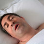 Man in his forties (40s) snoring in bed with type 2 diabetes and OSA.
