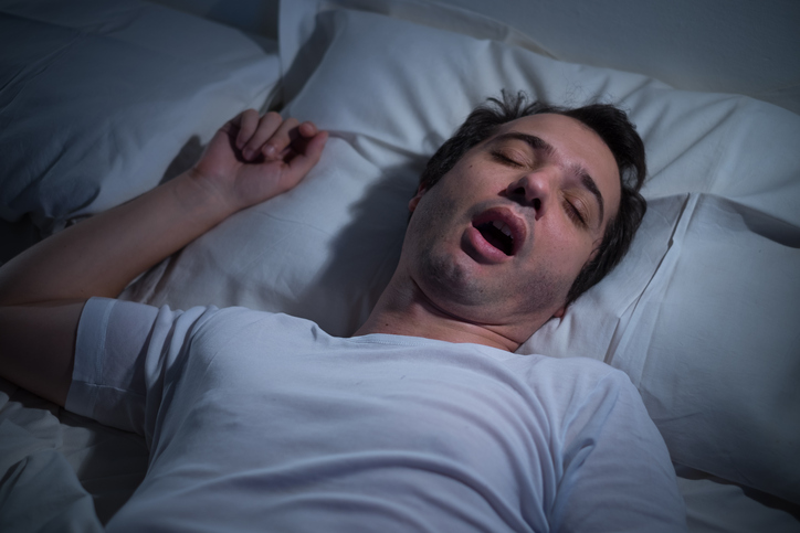 Man is snoring in bed due to sleep apnea, which is suspected to lower life expectancy.
