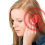 Girl holds hand on her ear because of her tinnitus, which is becoming worse due to an increase in her serotonin.