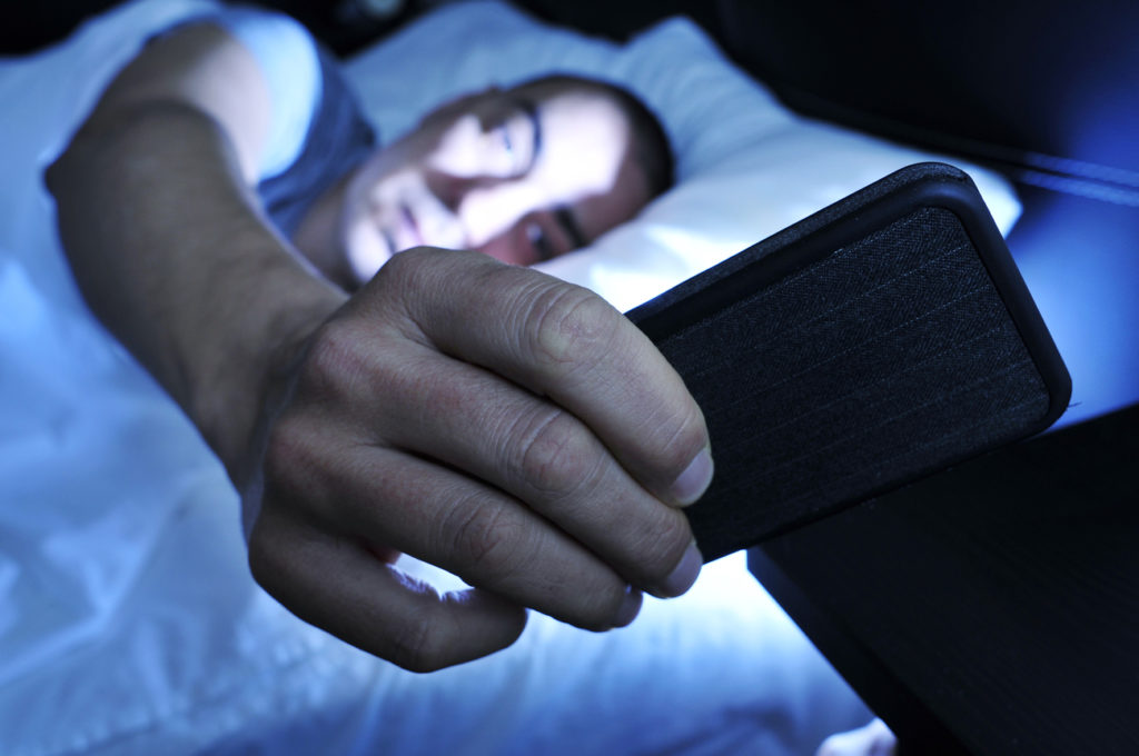 Closeup of a young man in bed looking at the smartphone at night, which affects sleep quality.