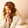 Dry coughs can be indicative of more serious health issues. This image depicts a woman in a blanket, suffering from a dry cough.