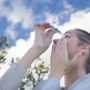 A woman is putting in eyedrops against a blue sky. Are allergies genetic?