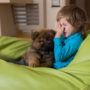 A little boy with pet allergies cuddles up next to a puppy in a green beanbag chair.