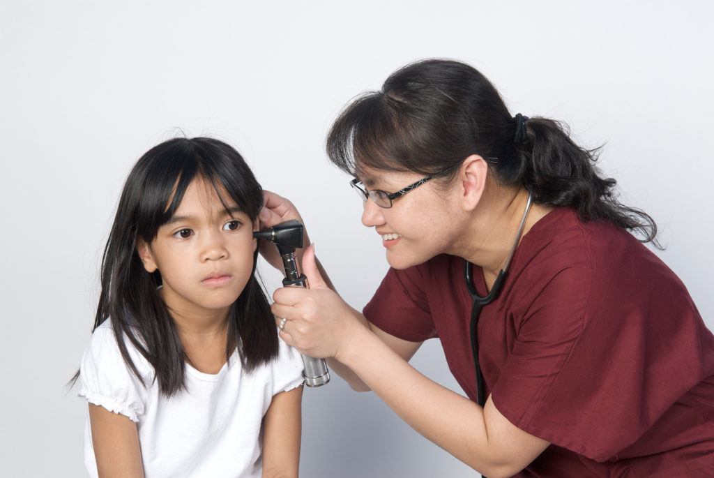 A young girl gets checked for middle ear infections by a doctor.