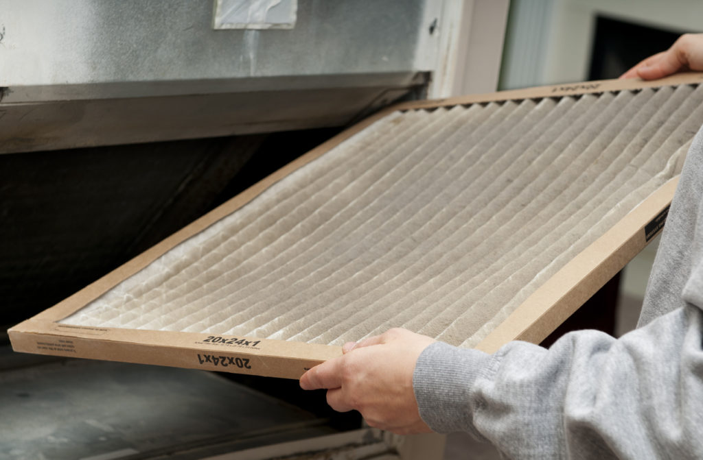 A man changes the filter inside his air purifier, which helps reduce indoor allergens.