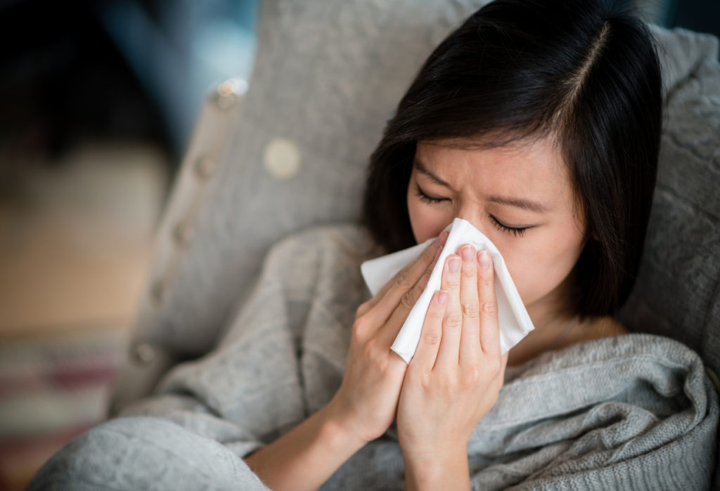 A woman with a tissue to her nose is suffering from allergies and may benefit from sublingual immunotherapy.