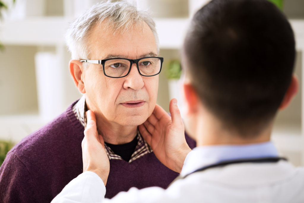 A man is at the doctor's office, receiving treatment for swallowing disorders.