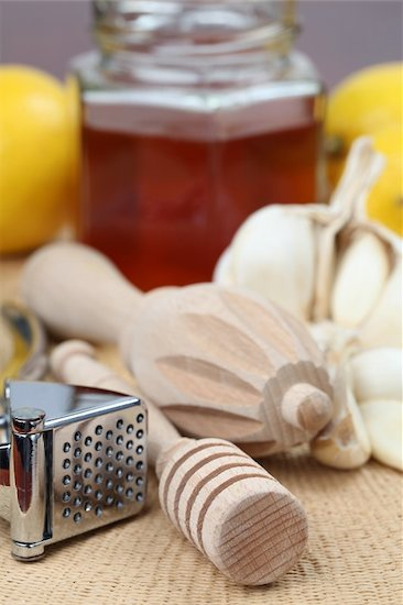 Honey dipper, juicer and garlic press with honey, lemons and garlic as natural medicine to aid against dry sinuses. Focus on foreground.