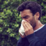 A man with a chronic runny nose uses tissues for relief.