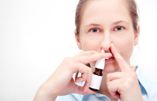 A woman uses saline spray to relieve her nasal congestion.