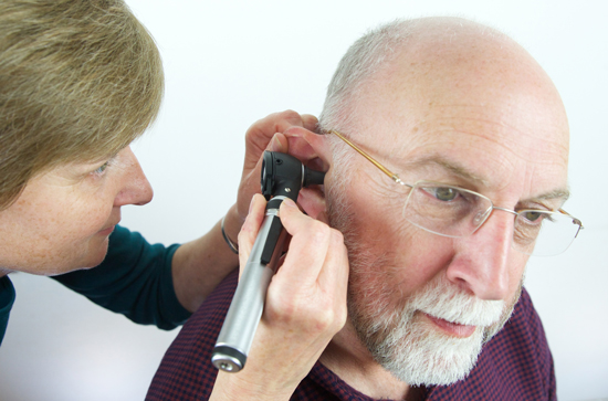 A physician examines a patient's tympanic membrane using an otoscope.